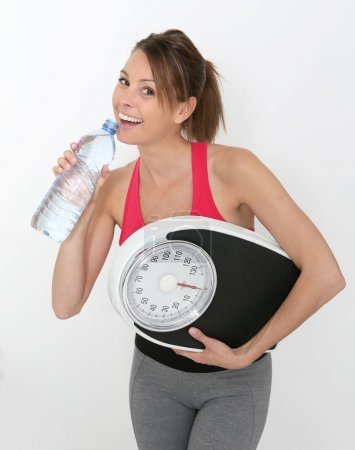 Girl with bottle of water and scale