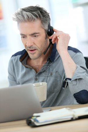 Photo for Mature man teleworking from home with laptop - Royalty Free Image