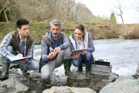 Biologist with students testing river water