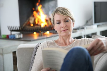 Photo for Middle-aged woman reading book by fireplace - Royalty Free Image