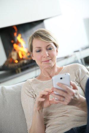 Foto de Mujer de mediana edad enviando un mensaje con teléfono inteligente - Imagen libre de derechos