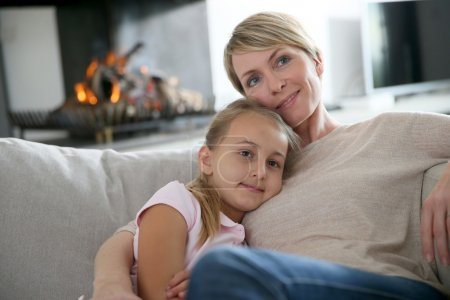 Photo for Mother and daughter relaxing by fireplace, laying in couch - Royalty Free Image