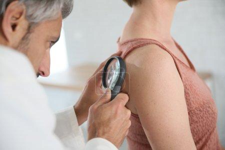 Photo pour Dermatologue, grain de beauté de la femme en regardant avec loupe - image libre de droit