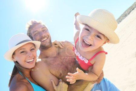 Foto de Padres alegres con niña en brazos en la playa - Imagen libre de derechos
