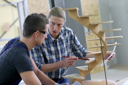 Photo for Apprentice with adult in carpentry school working on wood - Royalty Free Image