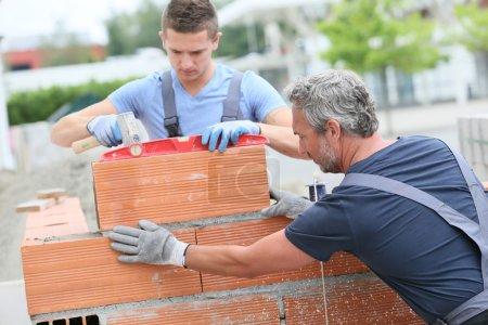 Photo pour Maçon avec stagiaire dans la construction, construction mur - image libre de droit
