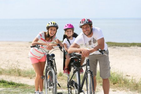 Family riding bikes on a sandy path