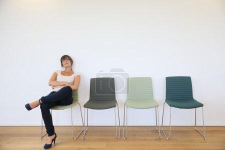Photo pour Jeune femme dans la salle d'attente s'ennuyer - image libre de droit
