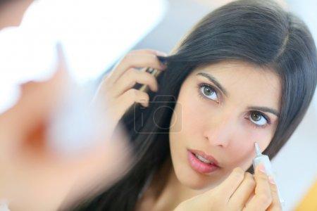 woman applying concealer