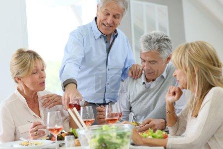 Photo pour Groupe de personnes âgées déjeunant ensemble à la maison - image libre de droit