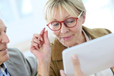 Senior woman trying  eyeglasses on