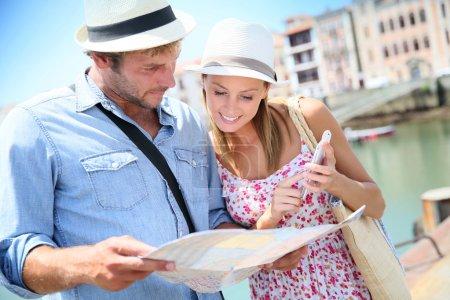 Photo pour Couple de touristes à la station balnéaire regardant la carte de la ville - image libre de droit