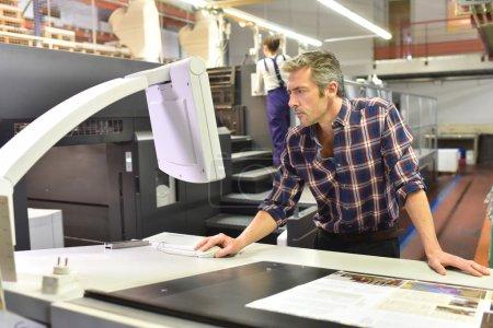 Man working on printing machine