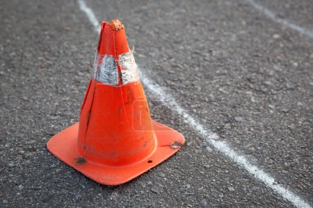 Old orange striped cone on road.