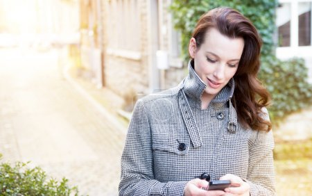 Photo for Businesswoman use her mobile phone outdoor in a historic village - Royalty Free Image