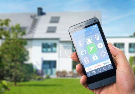 Photo pour Maison intelligente, domotique, appareil avec app icônes. L'homme utilise smartphone avec application de sécurité à la maison intelligente pour déverrouiller la porte de la maison. Accueil Smart Device - domotiques - image libre de droit