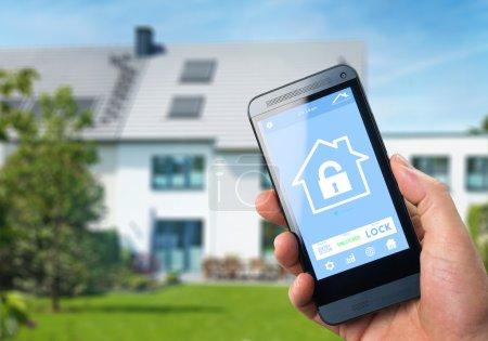 Photo pour Maison intelligente, domotique, appareil avec icônes app. Homme utilise smartphone avec application de sécurité de la maison intelligente pour déverrouiller la porte de la maison. Appareil de maison intelligente - Contrôle à domicile - image libre de droit