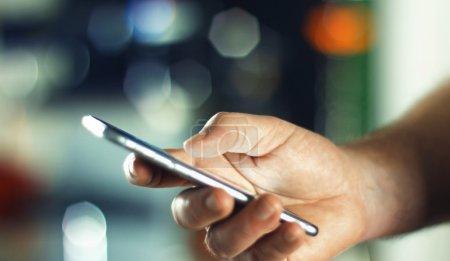 Photo pour Homme utilisant un téléphone portable dans le bureau avec un fond flou avec de l'espace pour le texte . - image libre de droit
