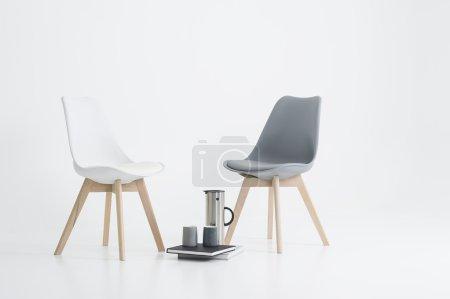 Photo pour Deux chaises modernes avec une portion de café dans une fiole élégante avec deux tasses reposant sur des livres à couverture rigide sur le sol entre les deux, sur blanc - image libre de droit