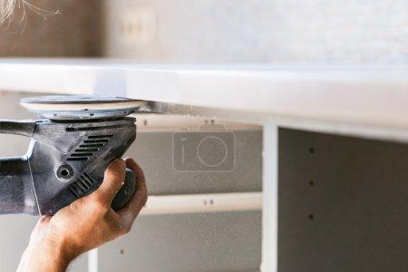Photo pour Installation nouvelle table dans la cuisine - travailleur finition plan de travail de la pierre artificielle de ponceuse - image libre de droit