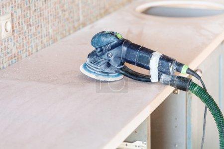 Photo pour Installation nouvelle table dans la cuisine - Ponceuse orbitale sur comptoir nouveau de la pierre artificielle - image libre de droit