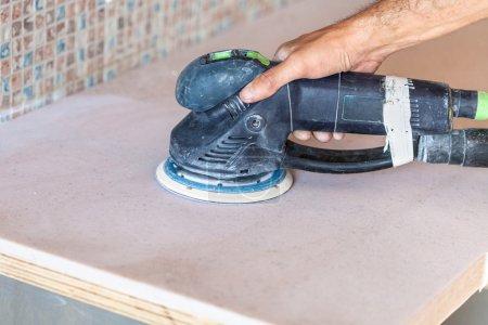 Photo pour Installation nouvelle table dans la cuisine - travailleur ponçage du comptoir de la pierre artificielle de ponceuse - image libre de droit