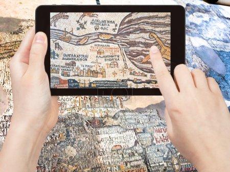 Photo pour Concept de voyage - tournages touristiques photo de l'ancienne carte byzantine de Terre Sainte, Madaba sur smartphone, Jordanie - image libre de droit
