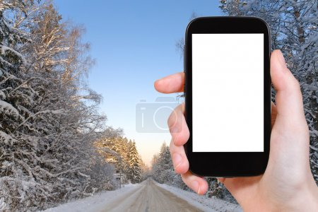 photo of winter road in snowy russian forest