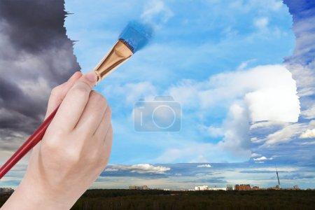 Paintbrush paints blue sky on rainy clouds