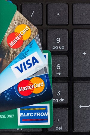 Photo for MOSCOW, RUSSIA - DECEMBER 8, 2105: above view of plastic VISA and MasterCard, VISA ELECTRON credit and debit cards on black computer keyboard. - Royalty Free Image