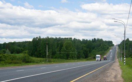 Photo pour Camions sur la route à travers les bois - image libre de droit
