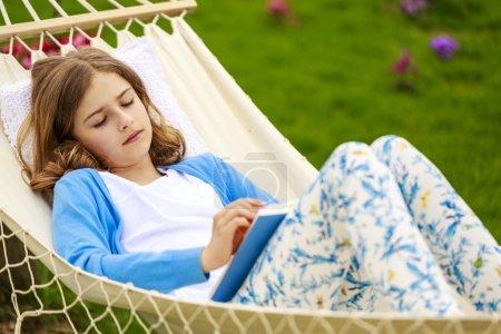 Photo pour Fille lisant un livre dans un hamac dans le jardin - image libre de droit