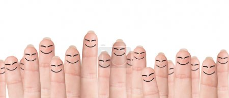 Photo for Many fingers with drawn faces stands on the green background - Royalty Free Image
