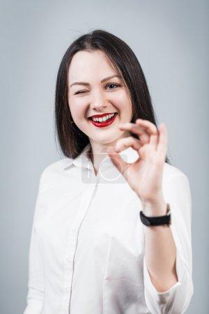 Photo pour Jeune belle femme montre OK signe sur le fond gris - image libre de droit