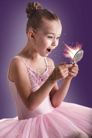 Photo pour Ballerine danseuse pour enfants en tutu rose regardant dans le miroir magique - image libre de droit