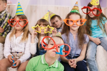 Photo for Large group of diversity looking kids, boys and girls sitting on the couch at home, hugging, smiling and laughing - Royalty Free Image