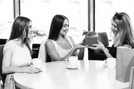 Photo pour Bonne humeur jeune femme surprenante d'un ami avec un cadeau au café - image libre de droit