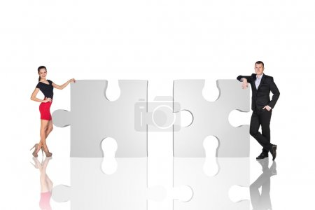 Photo for Two business people are standing near puzzle parts in order to succeed on the white background. - Royalty Free Image