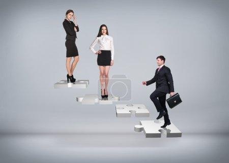 Photo pour Les gens d'affaires se tiennent sur les escaliers du puzzle sur le fond gris - image libre de droit