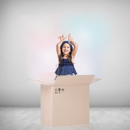 Photo for Beautiful little girl inside a cardboard box on the gray background - Royalty Free Image
