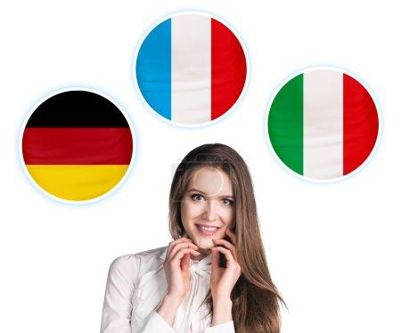 Foto de Mujer joven rodeada de burbujas de diálogo con las banderas de los países. Alemania, Italiano, Checo. Aprendizaje del concepto de lenguas extranjeras. - Imagen libre de derechos