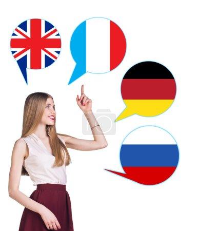 Foto de Mujer joven rodeada de burbujas de diálogo con las banderas de los países. Alemania, Gran Bretaña, Rusia, Checo. Aprendizaje del concepto de lenguas extranjeras. - Imagen libre de derechos