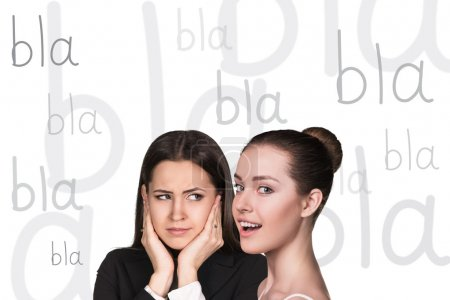 Photo for Two beautiful women gossiping on white background - Royalty Free Image