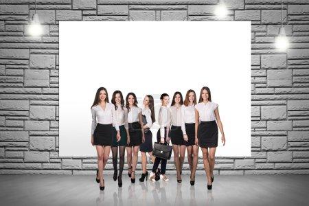 Photo pour Groupe de gens d'affaires se tient sur le fond du mur de briques - image libre de droit