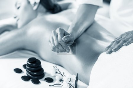 Photo for Young beautiful woman enjoying massage on the table at spa center - Royalty Free Image