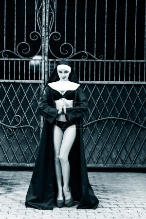 Sexy nun stands near the gate