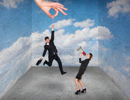 Photo pour Grande main tenant homme d'affaires dans une pièce rugueuse avec l'impression du ciel - image libre de droit