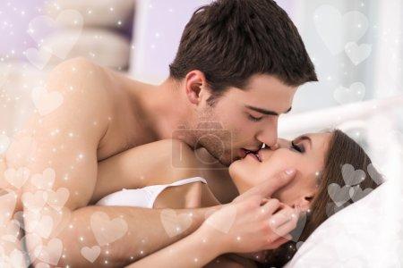 Photo pour Beau jeune couple d'amoureux couché dans son lit et s'embrasser - image libre de droit