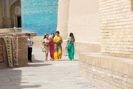 Photo pour Uzbek people are walking along the street at Itchan Kala, Khiva, Uzbekistan. Itchan Kala is the walled inner town of the city of Khiva. Since 1990 it has been protected as a World Heritage Site. The old town retains more than 50 historic monuments an - image libre de droit