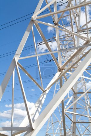 Bottom view power transmission lines against blue sky